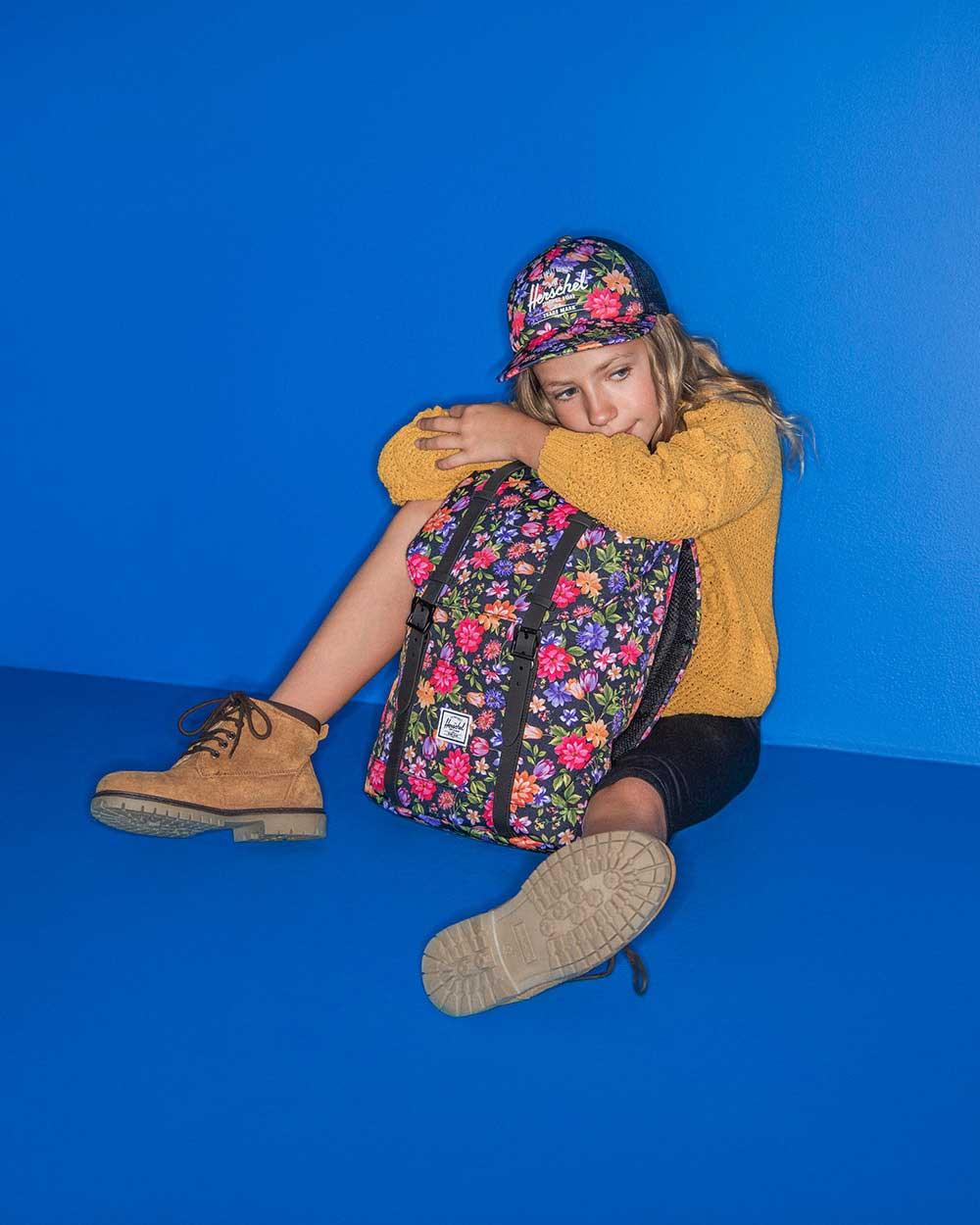 Un enfant est assis sur le sol avec un sac à dos Retreat gamme Jeune motif Garden Floral