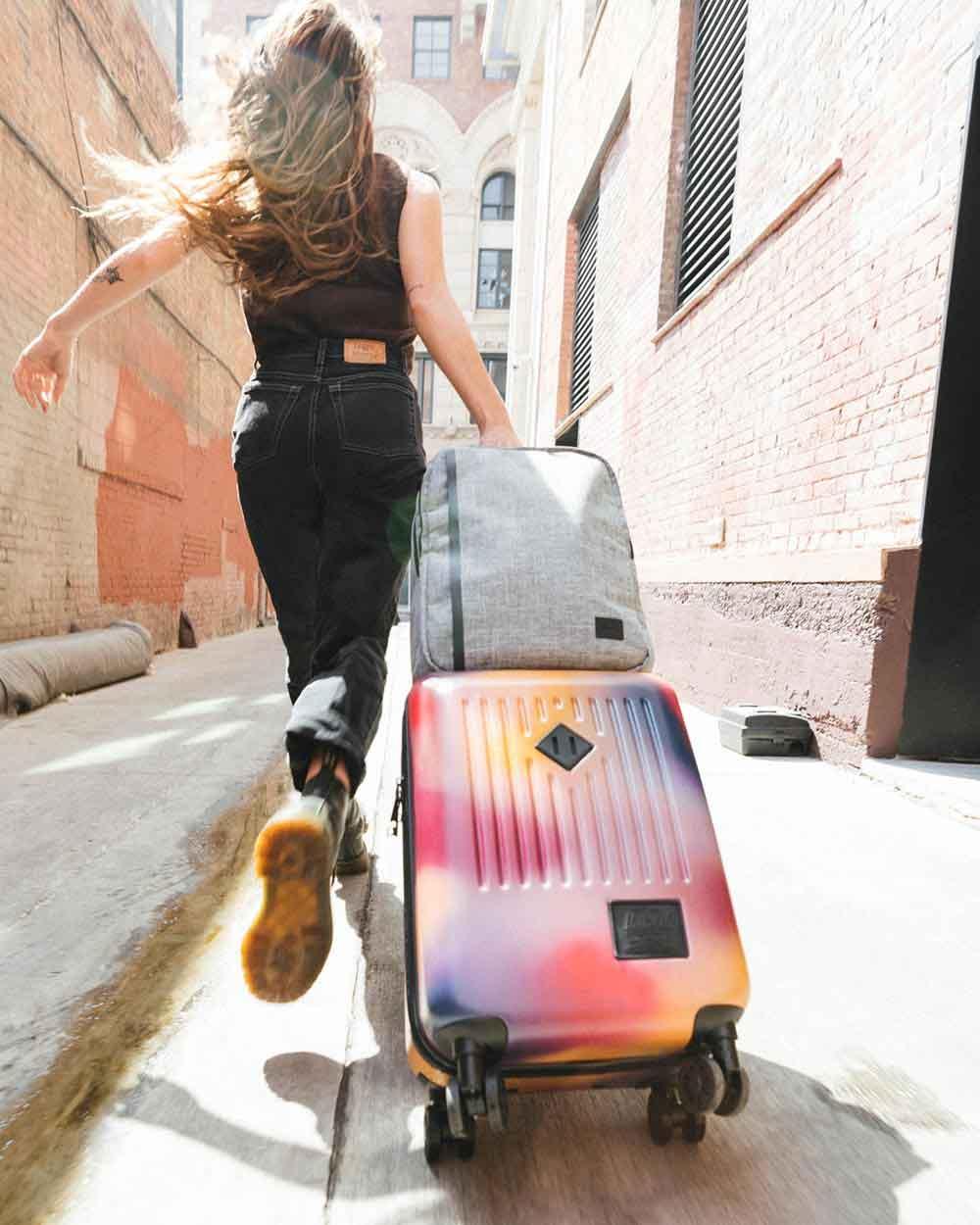 Une femme court dans une ruelle en tirant sa valise bagage à main Trade taille large motif dégradé Windsor Wine/Orange avec un sac à dos de voyage Raven Crosshatch sur le dessus.