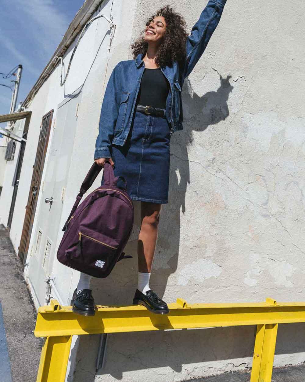 Une femme debout sur une balustrade tenant un sac à dos Blackberry Wine Nova de taille moyenne