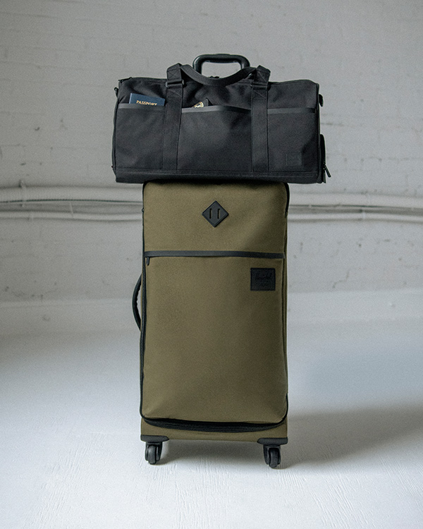 A Tech Novel Duffle in Black sitting atop a Highland Luggage 70L in Ivy Green