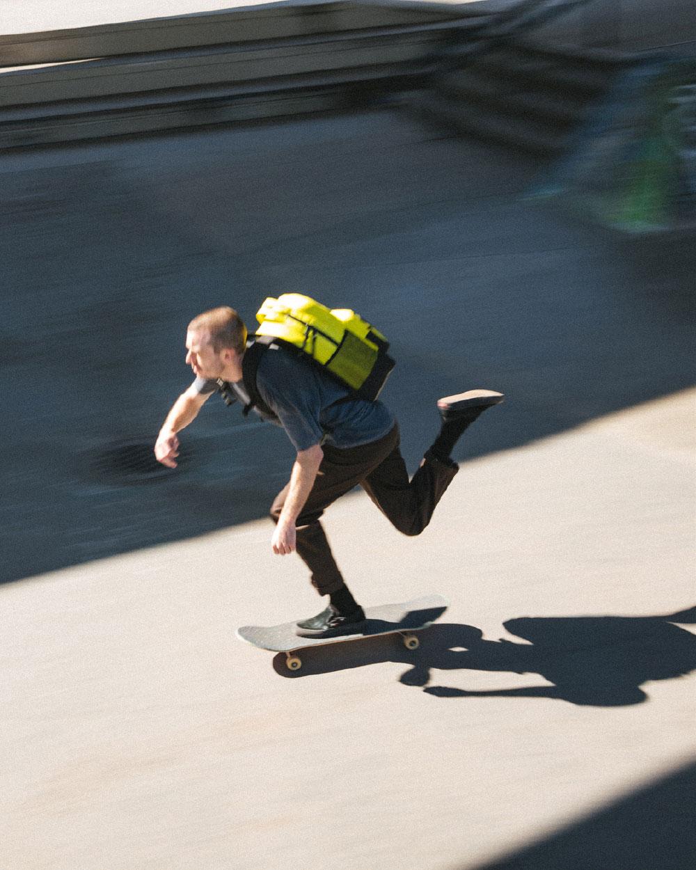 un homme en skateboard avec un sac à dos Miller isolant jaune sur