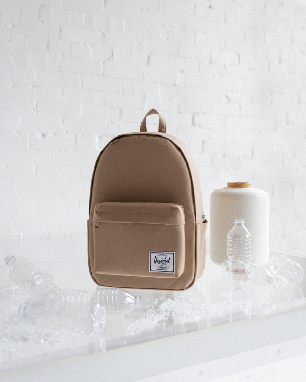 An Eco Classic Backpack XL next to the recycled materials it's made of.