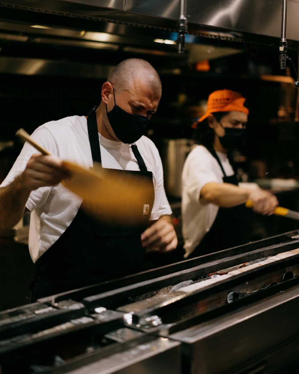 Chef Matt fans a narrow charcoal grill in his restaurant's kitchen