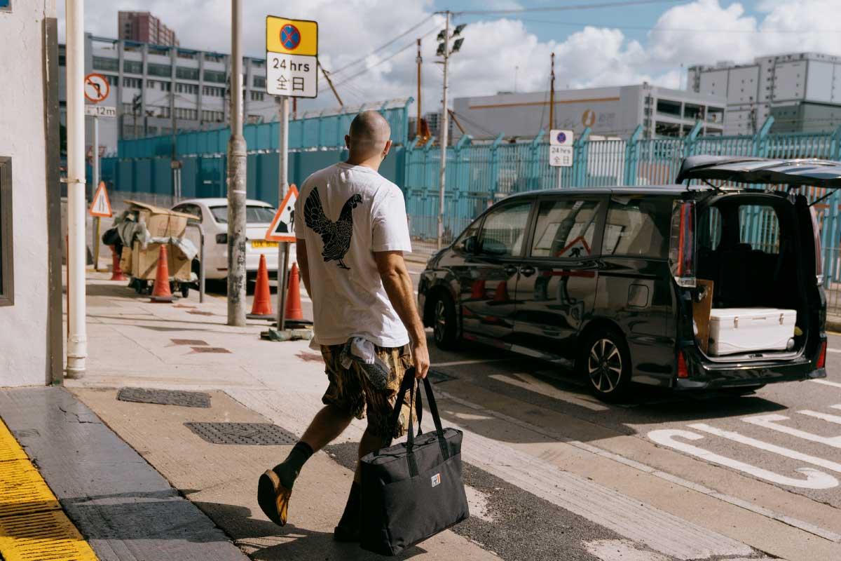 Une photo d'Erica Lall, une danseuse de New York marchant dans la rue avec un Nova Backpack Mid-Volume noir