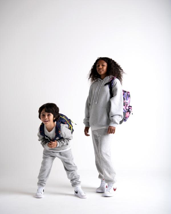 Quelques enfants portent des sacs à dos Little Herschel sur un fond gris