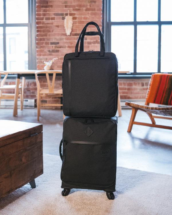 Un Highland Luggage Carry-On en noir et un sac cabas de voyage posé sur le dessus.